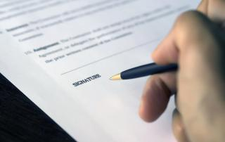 A hand is poising a pen over the signature area on a document.